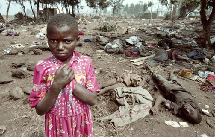 a girl stands amidst bodies in one of the genocide sites in 1994 in